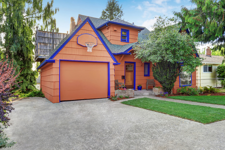 Coral exterior American house with blue trim with garage. View from driveway. Northwest, USA Stock Photo