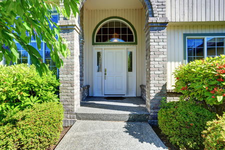 white door: American house exterior with concrete floor porch with columns. Northwest, USA Stock Photo