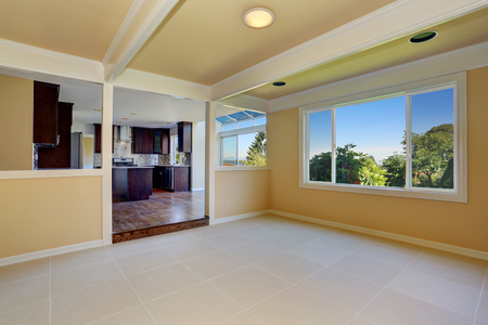 Open floor plan. Empty room with tile floor. View to kitchen room. Northwest, USA Archivio Fotografico