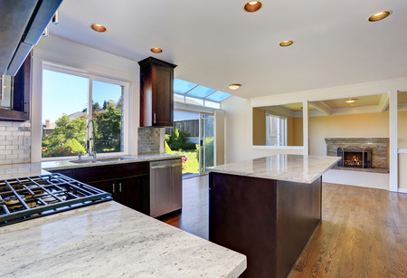 counter top: Kitchen room interior with deep brown cabinets with granite counter top, island and hardwood floor.Northwest, USA