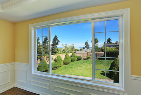 remodeled: Perfect view to backyard. Empty room interior with yellow walls and hardwood floor. Northwest, USA Stock Photo