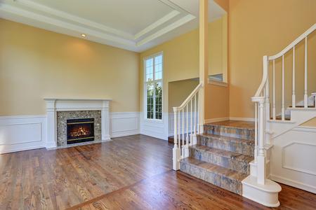 Open floor plan living room interior with hardwood floor and fireplace. Northwest, USA