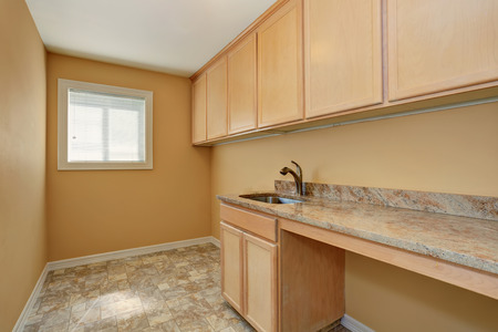 laundry room: Empty laundry room with cabinets with granite counter top and sink. Also tile floor. Northwest, USA