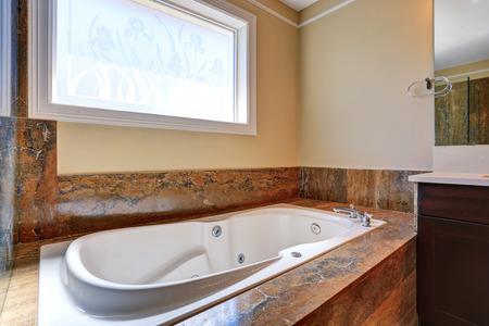 northwest: Luxury bathroom interior with white bath tub with marble trim. Northwest, USA