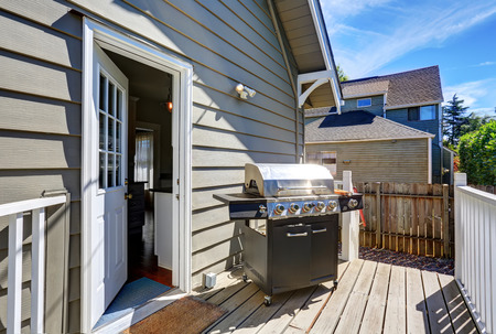 white trim: Wooden walkout deck with barbecue. Blue siding house with white trim. Northwest, USA