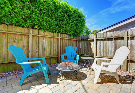 fenced: Fenced backyard with small patio area. Tile floor and green bushes. Northwest, USA