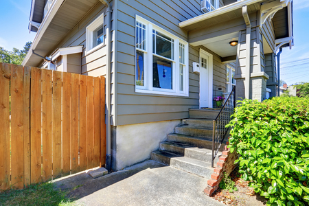 wooden fence: Concrete floor porch of siding house. Wooden fence and green bushes. Northwest, USA