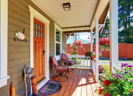 View of cozy small covered porch with chairs and flower pots. Northwest, USA
