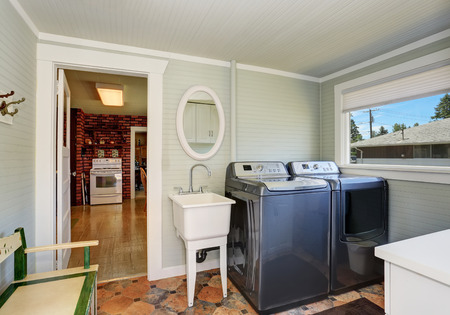 Laundry room interior with gray appliances, vintage sink and brown tile floor. Northwest, USA