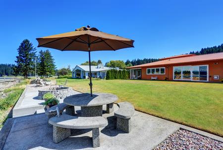back yard: Back yard with stone patio table set and fire pit. One story orange house exterior.   Luxury landscape design. Northwest, USA Stock Photo