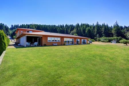 back yard: Orange house exterior. Back yard with well kept lawn. Northwest, USA Stock Photo