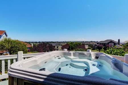 hot tub: Close-up of hot tub. Luxury house exterior. Blue sky background. Northwest, USA Stock Photo