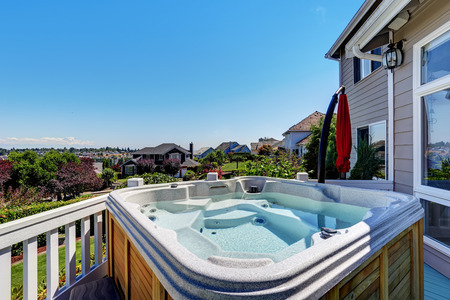 Close-up of wooden hot tub. Luxury house exterior. Blue sky background. Northwest, USA Stock Photo