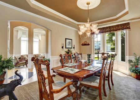 diseño interior precioso comedor con muebles de época, ventanas francesas. elegante lámpara de araña por encima de conjunto de mesa de madera tallada. Noroeste, EE.UU.
