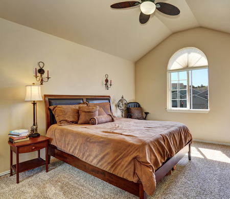 northwest: Upstairs bedroom with vaulted ceiling and arch window. Queen size bed has brown bedding. Northwest, USA