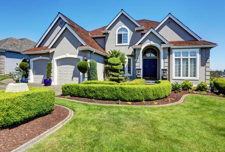 Luxe woonhuis met perfect onderhouden voortuin en blauwe hemelachtergrond. Northwest, VS.