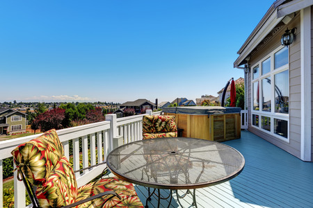 Wooden walkout deck with outdoor settees and hot tub. Blue sky background. Luxury house exterior. Northwest, USA Stock Photo