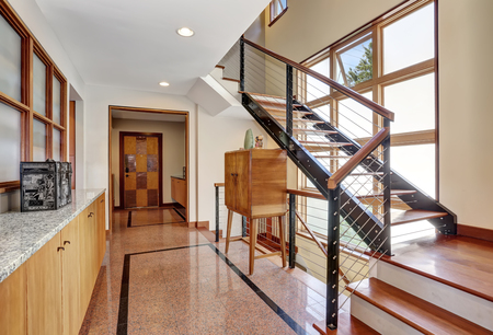 tile flooring: Long hallway interior with polished granite tile flooring, modern metal staircase and cabinets. Northwest, USA