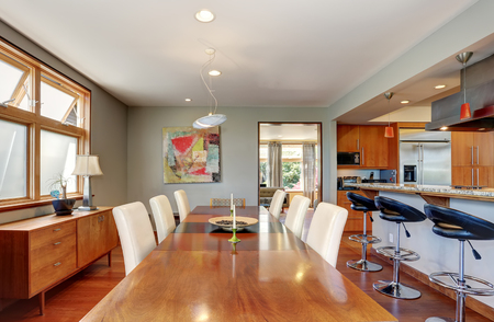 dining table and chairs: Large wooden dining table with white leather chairs in cozy house. Northwest, USA Stock Photo