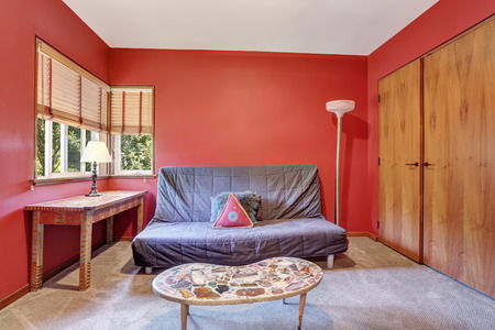Lovely red sitting room in cozy house with gray sofa and coffee table with stone decor. Northwest, USA 版權商用圖片