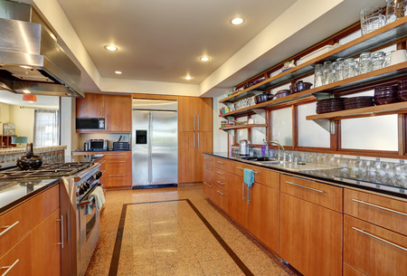 polished granite: Kitchen interior with long wooden cabinets and shelves. Stainless steel appliances and polished  granite flooring. Northwest, USA
