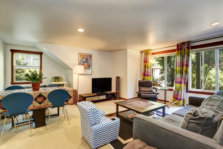 Bright Family room interior connected with dining area. Comfortable gray loveseat, leather chair and colorful curtains. Northwest, USA Stock Photo