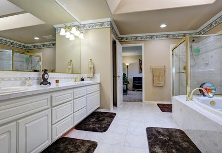 Bello interiore bagno di lusso. Bianco moderno vanità bagno, vasca da bagno con finiture in piastrelle e doccia proiettato in vetro. Northwest, Stati Uniti d'America
