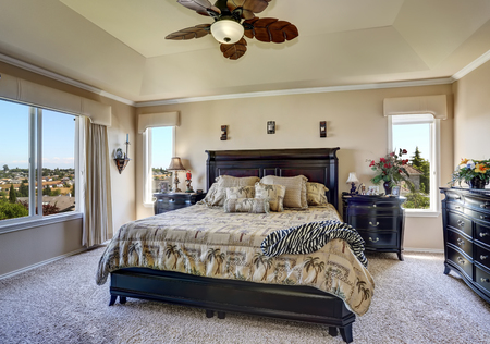 king size bed: Luxury interior of master bedroom with black furniture. King size bed with headboard and tropical patterned bedding. Northwest, USA
