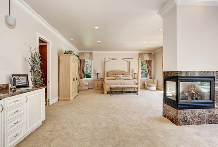 Large master creamy tones bedroom interior in luxury home with queen size canopy bed . Glass fireplace with burning fire. Northwest, USA