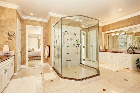Mooi luxe marmeren badkamer interieur in beige kleur. Grote glazen inloopdouche en twee ijdelheidskasten. Noordwest, Verenigde Staten