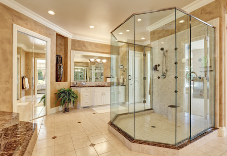 Beautiful luxury marble bathroom interior in beige color. Large glass walk in shower. Northwest, USA