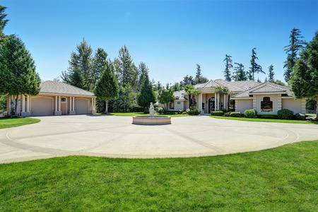 wood door: Suburban family house with fountain statue in the front yard, asphalt driveway and detached garage. Luxury residential house with large windows, trees around and blue sky background. Northwest, USA
