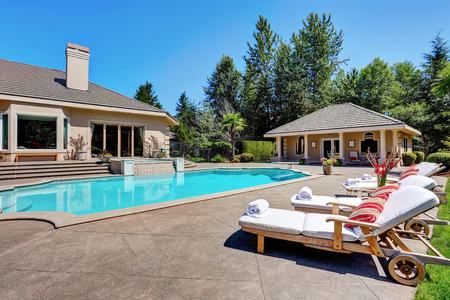 Great backyard with swimming pool and lounge chairs in American Suburban luxury house. Northwest, USA