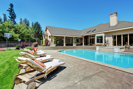 lounge chairs: Great backyard with swimming pool and lounge chairs in American Suburban luxury house. Northwest, USA