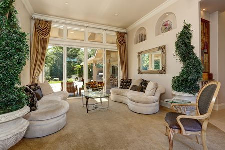 entryway: Amazing Luxury entrance Hallway interior with decorative trees in pots and modern beige settees. Northwest, USA Stock Photo