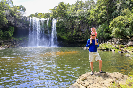 Father with his daughter on his shoulders, enjoying a beautiful waterfall view.  Kerikeri, Northland New Zealand.