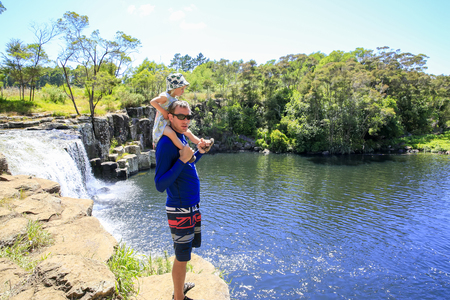 Young father with daughter on his shoulders enjoying Kerikeri waterfall. Top view.  Northland New Zealand. Stock Photo