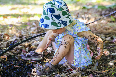 Cute little girl with is sitting on the ground and playing in mud Stock Photo