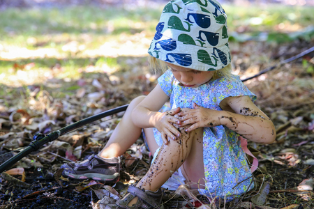 sitting on the ground: Cute little girl with is sitting on the ground and playing in mud Stock Photo