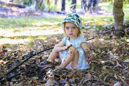 Leuk meisje met blauwe ogen zit op de grond en spelen in de modder Stockfoto
