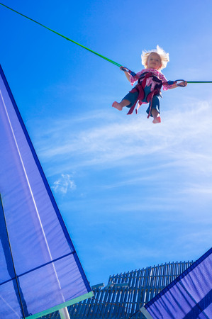 bungee jumping: Cheerful Little blond girl jumping on the trampoline, bungee jumping, blue sky background. Foto de archivo