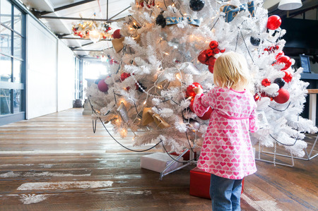 suddenness: Little girl in a pink shirt is standing by white Christmas tree decorated with colorful balls.
