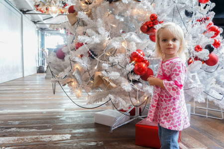 Portrait of Little girl in a pink shirt is standing by white Christmas tree decorated with colorful balls.