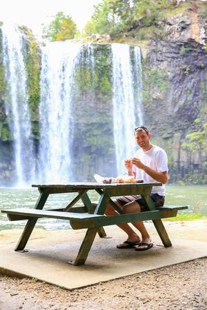 Tourist sitting at the table and having meal outdoors. Whangarei waterfall, New Zealand