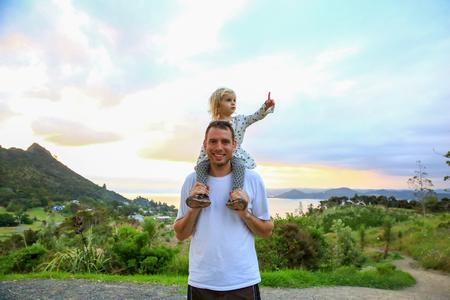 彼の肩に小さな娘と若い幸せな父。マウント マナイア。ニュージーランド
