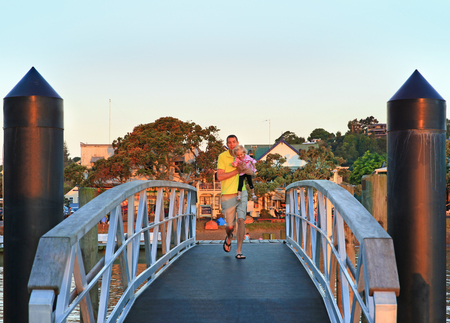 Happy young father with his little daughter run across the small bridge early in the morning. Russel, NEw Zealand Stock Photo