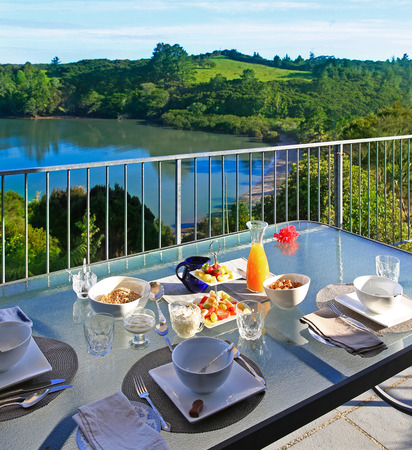 sky brunch: Outside served colorful breakfast table at the patio area with perfect water view. New Zealand Stock Photo
