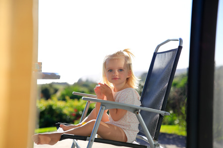 cute little girl: Outdoor photo of cute little girl having sunbath at chair and enjoying her leisure time. Stock Photo