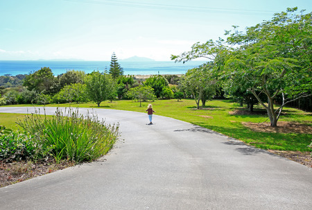 Little blond girl is strolling along the garden and enjoying spectacular view of Waipu in New Zealand.