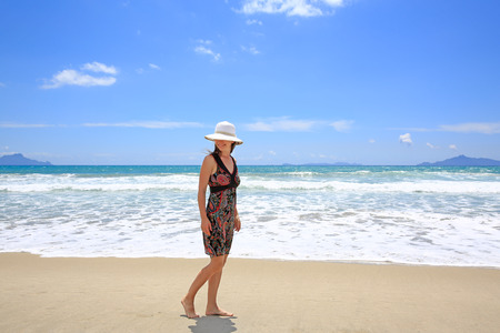 new zealand beach: Young pretty smiling woman in a hat is strolling along Sandy Beach. Waipu Area, Northland, North Island, New Zealand